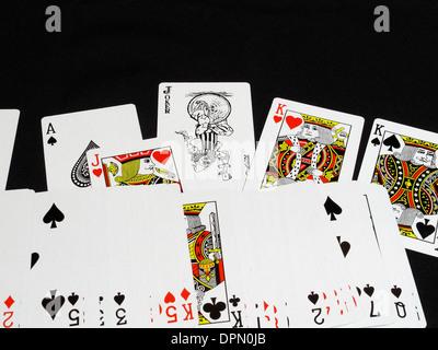 ein Kartenspiel mit dem Joker prominent in der Mitte der Packung verteilt - Stockfoto