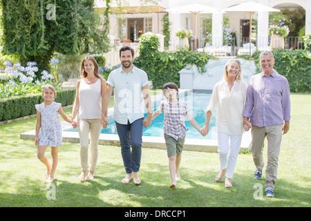 Mehr-Generationen-Familie Hand in Hand und Wandern im Hinterhof - Stockfoto