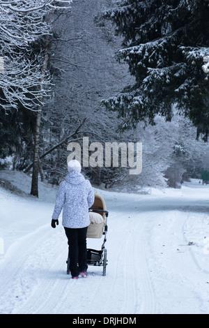 Eine Frau schiebt einen Kinderwagen oder Buggy in einem verschneiten Wald - Stockfoto