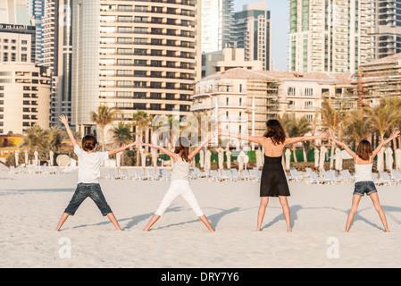 Familie stehen in einer Reihe am Strand, Hand in Hand, Rückansicht - Stockfoto