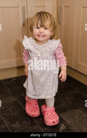 18 Monate altes Mädchen Mutter Crocks Schuhe tragen. - Stockfoto