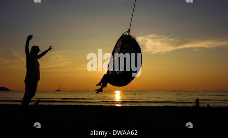 Spielen in einem Seil Schwung bei Sonnenuntergang an einem Strand auf der Insel Koh Kood, Thailand. - Stockfoto