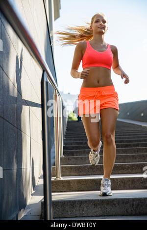 Junge weibliche Läufer bewegen Sie Stadt Treppe - Stockfoto