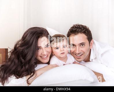 Porträt des jungen Familienglück zu Hause am Morgen, liegend im Bett, Mutter und Vater Spaß mit Töchterchen - Stockfoto