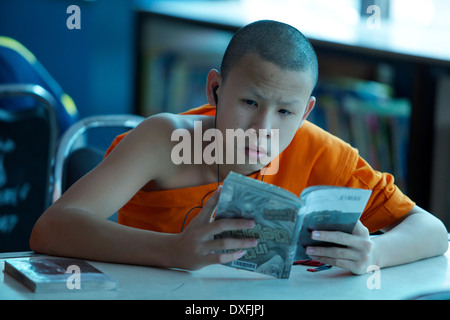 Junger Mönch ein Buch zu lesen, während Sie Musik hören - Stockfoto