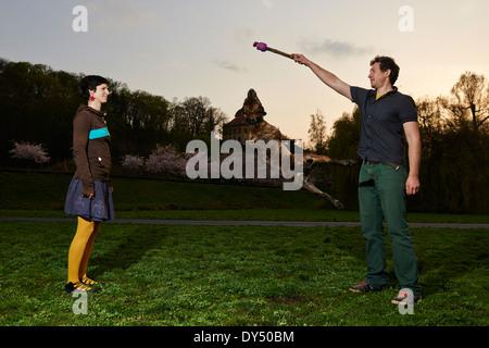 Glückliche junge Paar spielen mit ihrem springenden Hund im Park - Stockfoto