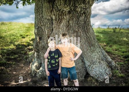 Zwei Brüder stehen unter einer alten Eiche. - Stockfoto