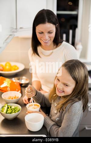 Glückliche Mutter und Tochter bereitet Salat in Küche - Stockfoto