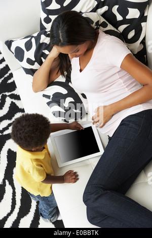 Draufsicht von Mutter und Sohn auf Sofa mit Digital-Tablette - Stockfoto