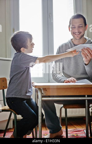 Vater holding Papierflieger für Sohn - Stockfoto