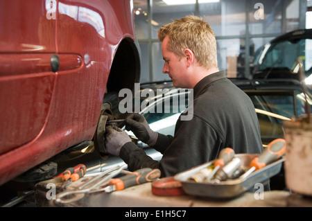 Ein Mechaniker in einer Garage ist die Überprüfung und Reparatur der Bremsen eines gehobenen Autos. - Stockfoto
