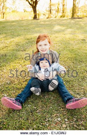 Porträt von Mädchen und Baby Bruder auf dem Rasen im park - Stockfoto