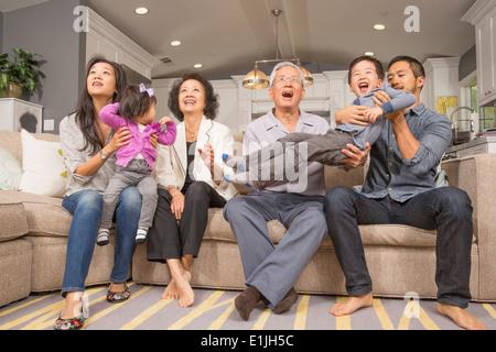 Drei-Generationen-Familie zusammen spielen auf sofa - Stockfoto