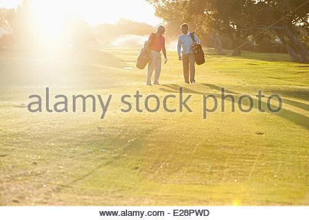 Männer tragen Golfbags auf Golfplatz - Stockfoto