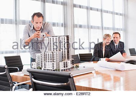 Architekten im Konferenzraum mit Gebäude Modell nehmen Foto mit Digitalkamera - Stockfoto