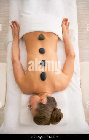 Entspannte junge Frau Verlegung auf Massagetisch und hot-Stone-Massage empfangen - Stockfoto