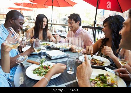 Gruppe von Freunden genießen Mahlzeit im Restaurant unter freiem Himmel - Stockfoto