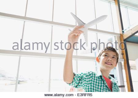 Jungen spielen mit Spielzeugflugzeug am Flughafen - Stockfoto