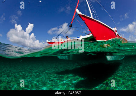 "Split Level Blick auf jungen Mann liest einen Buch an Bord 30ft Tiki Katamaran ""Abaco"". Exumas, Bahamas, Karibik. - Stockfoto"