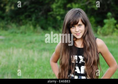 Mädchen Teen Teenager Übergang Alter 13 14 15 Jahre brünette Haare lange dunkle Natur Park Open-Air schönes Porträt - Stockfoto