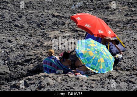 Menschen, die Schutz vor Wind und Sonne unter Sonnenschirmen in einer felsigen Senke - Stockfoto