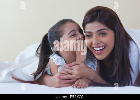 Mädchen in Mutters Ohr auf Bett Flüstern - Stockfoto