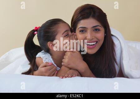 Niedliche Mädchen Flüstern in Mutters Ohr auf Bett - Stockfoto