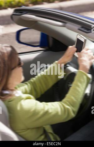 Reife Frau SMS während der Fahrt Sportwagen, USA - Stockfoto