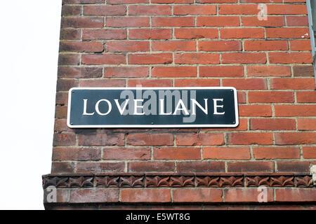 Liebe Lane Straße Namensschild auf der UK Gebäude aus rotem Backstein - Stockfoto