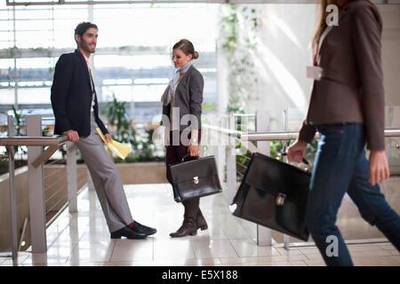 Unternehmer und Unternehmerinnen mit Aktentaschen im Konferenz-Center atrium - Stockfoto