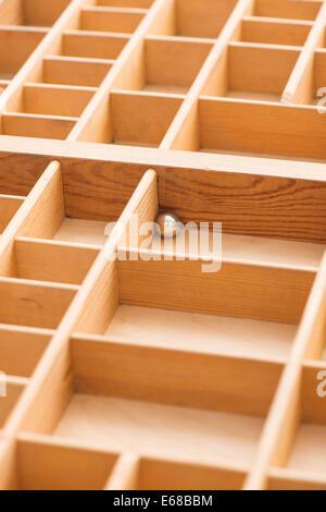 Kleine Stahlkugel in Holzkiste mit leere Felder. Konzeptbild von Einsamkeit, Einsamkeit und gefangen. - Stockfoto