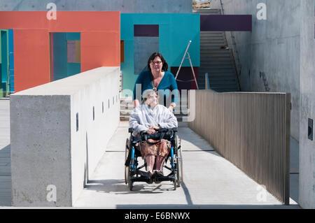 Eine ältere Dame wird hochgeschoben eine konkrete behindertengerechte Rampe im Rollstuhl durch ihre Pfleger oder - Stockfoto