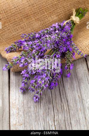 Lavendelblüten in einem Korb mit Sackleinen auf dem hölzernen Hintergrund - Stockfoto