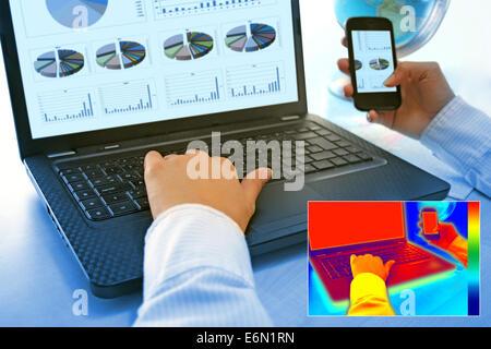 Infrarot-Thermografie-Bild zeigt die Hitze und Strahlung von Notebooks und Smartphones im Büro - Stockfoto