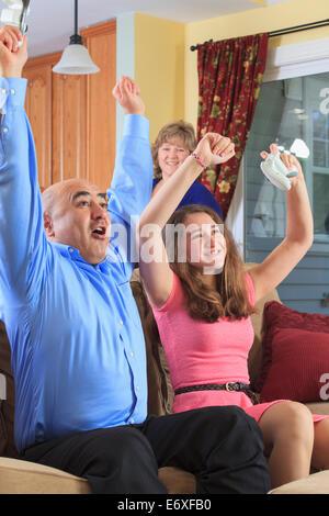 Vater und Tochter spielen auf ihrem Fernsehschirm und jubeln - Stockfoto