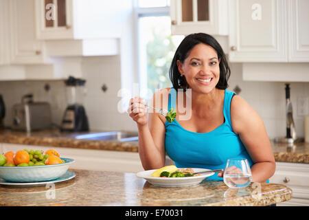 Übergewichtige Frau gesund Essen in der Küche - Stockfoto