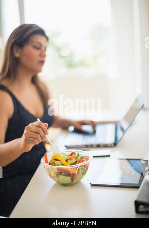 Frau Salat essen und mit Laptop im Büro - Stockfoto
