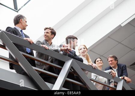 Team von Führungskräften, die miteinander reden, auf Balkon - Stockfoto
