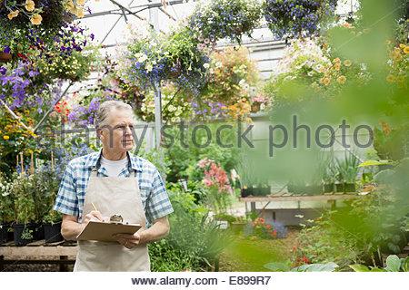 Arbeiter mit Zwischenablage in Pflanzen Gärtnerei Gewächshaus - Stockfoto