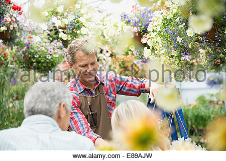 Arbeiter im Gespräch mit paar in Pflanzen Gärtnerei Gewächshaus - Stockfoto