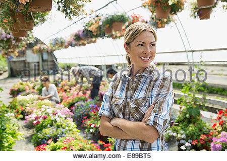 Lächelnde Arbeiter im Werk Gärtnerei Gewächshaus - Stockfoto