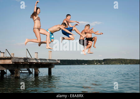 Fünf Jugendliche springen von einer Anlegestelle in See - Stockfoto