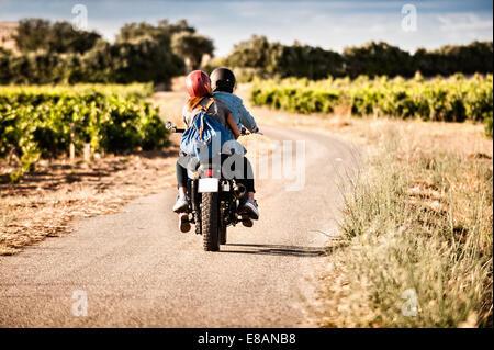 Rückansicht des Mitte erwachsenes paar Motorrad auf kurvigen Landstraße, Cagliari, Sardinien, Italien - Stockfoto