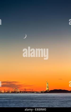 Freiheitsstatue unter einer steigenden Mondsichel bei Sonnenuntergang - Stockfoto