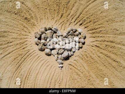 Herz aus Kieselsteinen in sand - Stockfoto