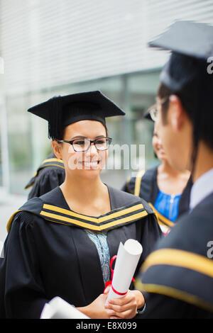 Student in Mütze und Mantel mit Freunden zu reden - Stockfoto