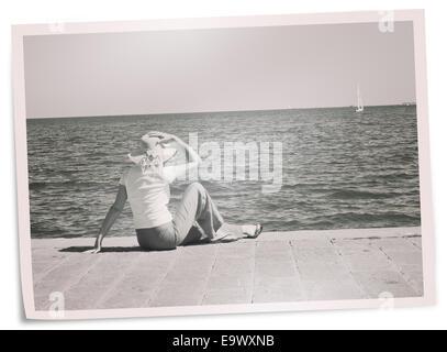 70er Jahre Stil Foto Frau Uhren Boot heraus zum Meer zu segeln. Träume, Reue, Zeit oder Reminiszenz Konzept. - Stockfoto