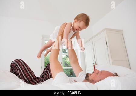Vater mit Tochter auf Bett spielen - Stockfoto