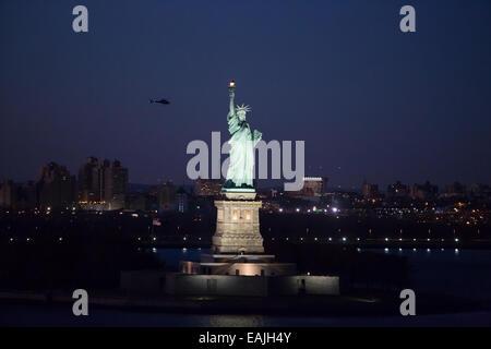 Nächtliche Foto der Statue of Liberty im Hafen von New York, New York, USA. - Stockfoto