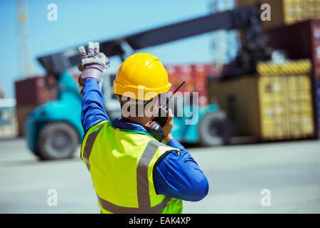 Arbeiter mit Walkie-talkie in der Nähe von Containern - Stockfoto
